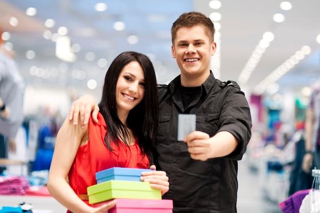 Gelukkig jong paar zakgeld bij kledingwinkel Gratis Foto