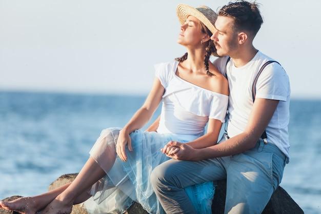 Gelukkig jong romantisch paar die op het strand ontspannen en op de zonsondergang letten Gratis Foto