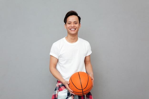 Gelukkig jonge aziatische man met basketbal Gratis Foto