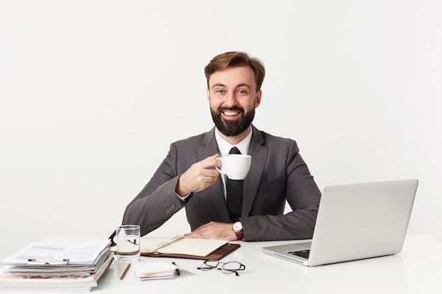 Gelukkig jonge bebaarde zakenman met kort bruin haar werken in een modern kantoor, met een kopje koffie voordat ze elkaar ontmoeten, glimlachend vrolijk naar voren zittend over de witte muur Gratis Foto