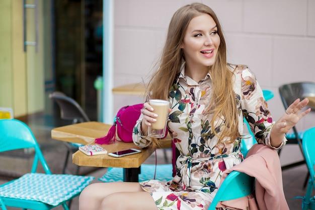 Gelukkig jonge hipster stijlvolle vrouw zitten in café lente zomer modetrend, koffie drinken Gratis Foto