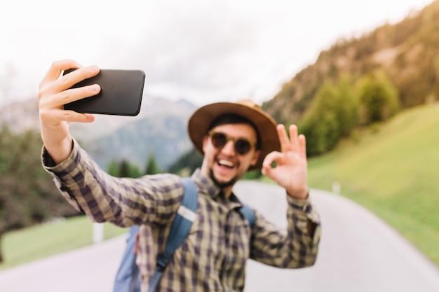 Gelukkig jonge man met blauwe rugzak selfie met glimlach en ok teken, staande op de weg maken Gratis Foto