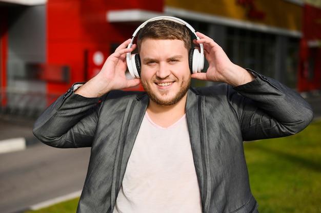 Gelukkig jonge man met een koptelefoon op zijn oren Gratis Foto