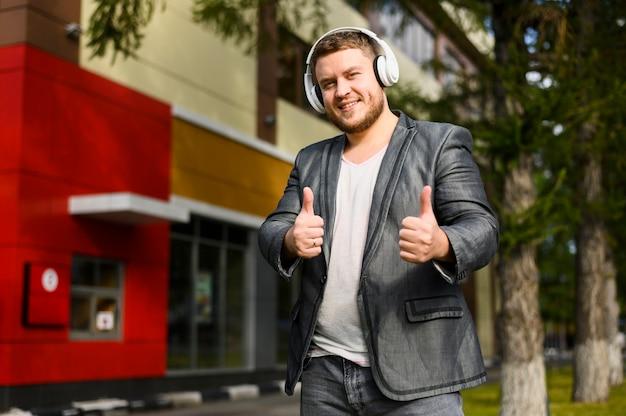 Gelukkig jonge man met koptelefoon camera kijken Gratis Foto