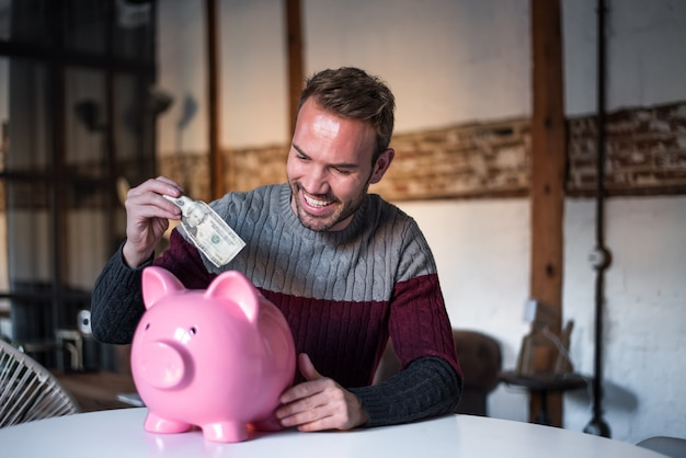 Gelukkig jonge man met spaarvarken Premium Foto