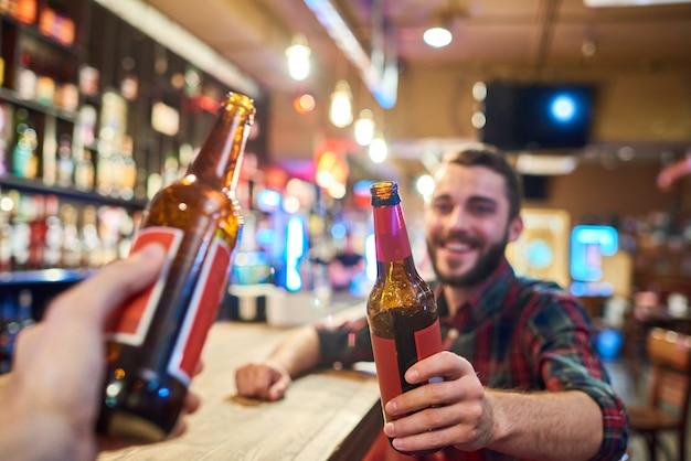 Gelukkig jonge man rammelende flessen met vriend in bar Premium Foto