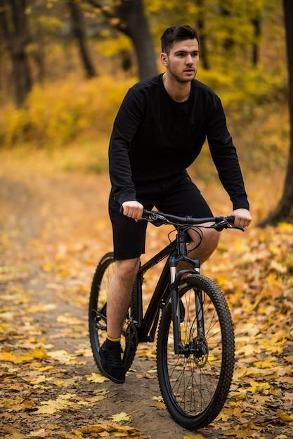Gelukkig jonge man wielrenner rijdt in het zonnige bos op een mountainbike. avonturen reis. Gratis Foto
