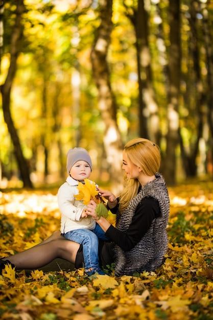 Gelukkig jonge moeder en haar zoontje tijd doorbrengen in de herfst park. Gratis Foto