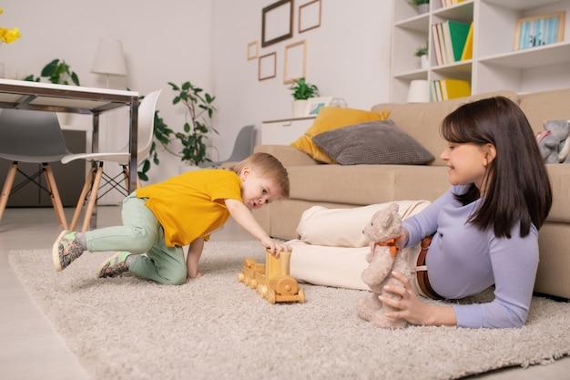 Gelukkig jonge moeder liggend op zacht tapijt thuis en speelgoed beer te houden terwijl haar zoon speelt met speelgoed trein Premium Foto