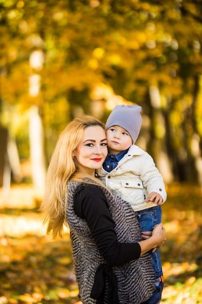 Gelukkig jonge moeder spelen met haar zoontje littlte op zonnige warme herfst- of zomerdag. prachtig zonsonderganglicht in de appeltuin of in het park. gelukkig gezin concept Gratis Foto