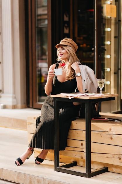 Gelukkig jonge vrouw draagt trendy zwarte schoenen en lange jurk ontspannen na een zware dag en koffie drinken. openluchtportret van glimlachend meisje in bruine glb en vacht wachtende vriend om iets te vieren. Gratis Foto