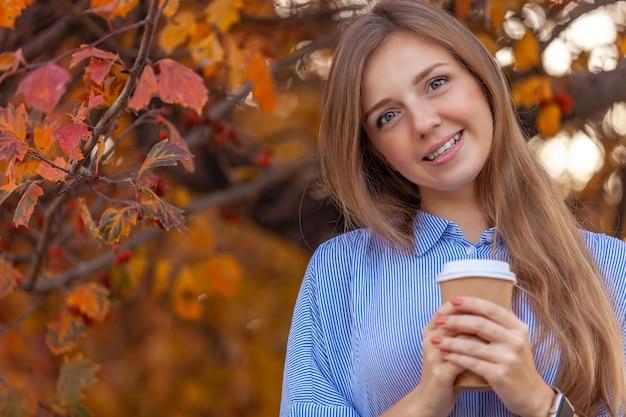 Gelukkig jonge vrouw met kopje koffie om te gaan op herfst rode bomen Premium Foto