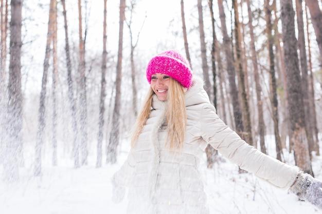 Gelukkig jonge vrouw speelt met een sneeuw op besneeuwde bossen buiten Premium Foto
