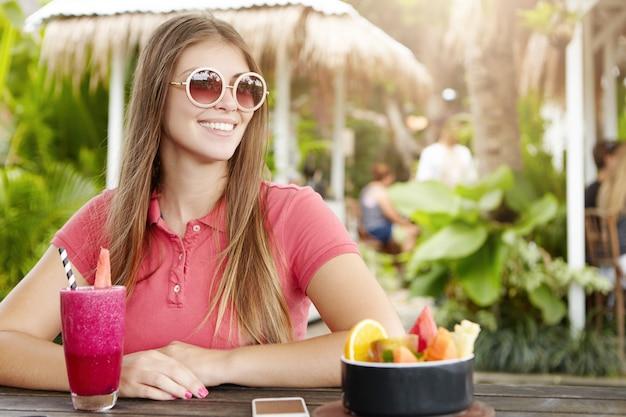 Gelukkig jonge vrouw trendy ronde zonnebril en poloshirt dragen genieten van vakantie, met verse bessen schudden in café. Gratis Foto