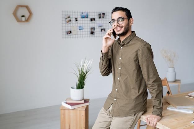 Gelukkig jonge zakenagent permanent door tafel in kantoor tijdens het raadplegen van een van de klanten door smartphone Premium Foto