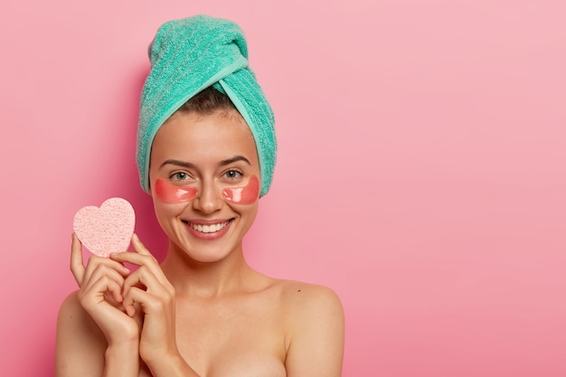 Gelukkig jongedame draagt collageen hydraterende plekken onder de ogen, houdt een spons voor het verwijderen van make-up, heeft schoonheidsbehandelingen, heeft een frisse huid na het nemen van een douche Gratis Foto