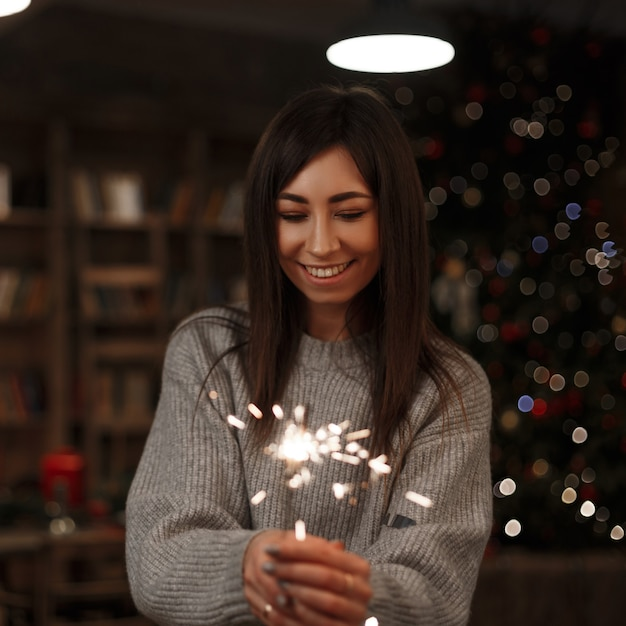 Gelukkig jongedame in een gebreide trui houdt een geweldig sterretje in haar hand in een vintage kamer. vrolijk kerstfeest en een gelukkig nieuwjaar. meisje lacht. Premium Foto