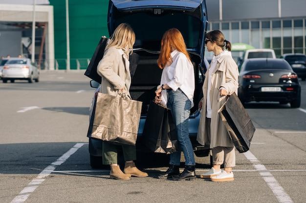 Gelukkig jongedame met boodschappentassen lopen op straat. Gratis Foto