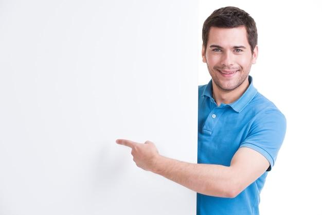 Gelukkig jongeman wijst vinger op een lege banner - geïsoleerd op wit. Gratis Foto