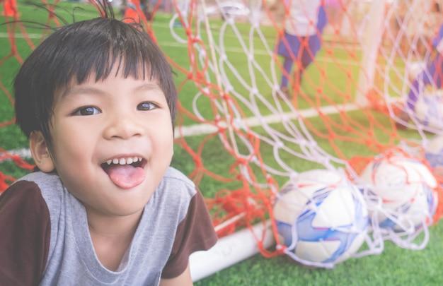 Gelukkig jongetje achter het doel op voetbal trainingsveld Premium Foto