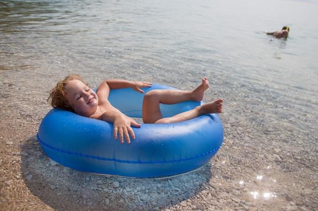 Gelukkig jongetje drijft op een opblaasbare ring in de zee Premium Foto