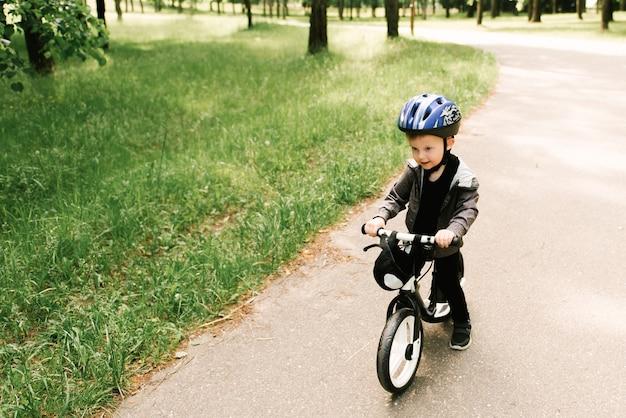 Gelukkig jongetje met een fiets die in het park loopt Premium Foto