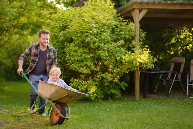 Gelukkig jongetje plezier in een kruiwagen duwen door papa in binnenlandse tuin op warme zonnige dag. Premium Foto