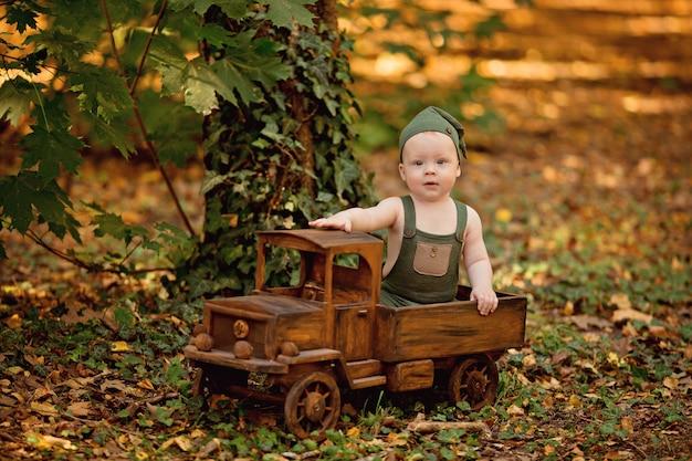Gelukkig jongetje zit in de speelgoedauto van houten kinderen buiten in de zomer Premium Foto
