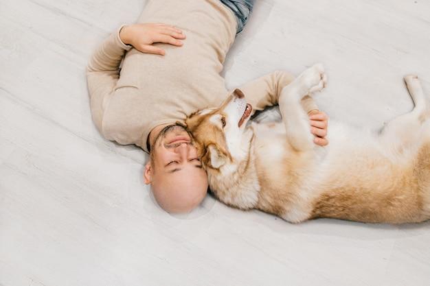 Gelukkig kale man met husky puppy ontspannen op de vloer. Premium Foto