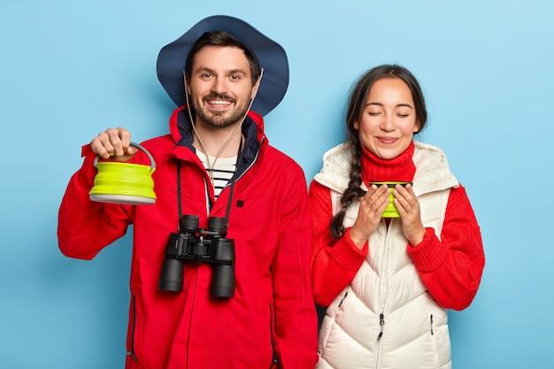 Gelukkig kampeerpaar drinkt vroeg in de ochtend koffie, brengt vrije tijd door op de camping in de buurt van vreugdevuur, draagt een verrekijker, stopt voor een pauze, draagt een warme outfit, geïsoleerd over blauwe muur Gratis Foto