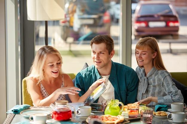 Gelukkig kaukasische vrienden rusten in café met maaltijd en plezier Premium Foto