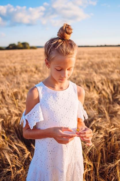Gelukkig kind in een tarweveld. mooi meisje in witte jurk in een strooien hoed met rijpe tarwe in handen Premium Foto
