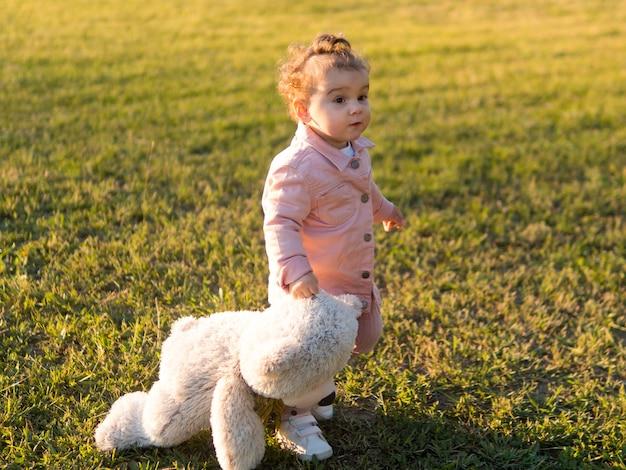 Gelukkig kind in roze kleding en zijn vriendelijke speelgoed Gratis Foto