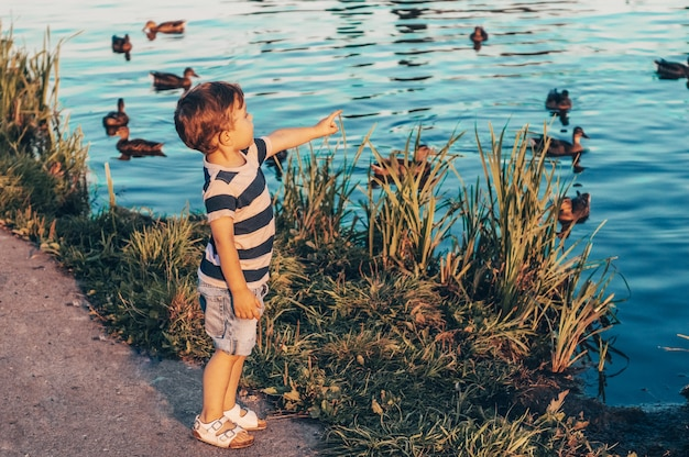 Gelukkig kind, kleine jongen kijkt naar beneden, peinzende blik en de gezwellen buitenshuis in handen houden. Premium Foto
