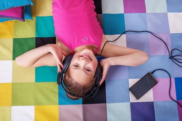 Gelukkig kind liegen en luisteren naar muziek. jeugd en muziek. Premium Foto