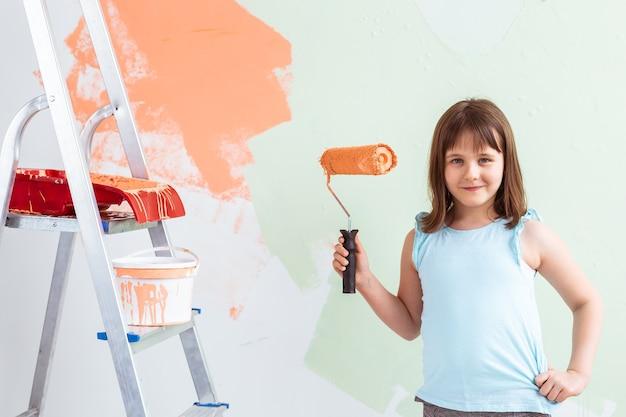 Gelukkig kind meisje schildert de muur met oranje verf, Premium Foto
