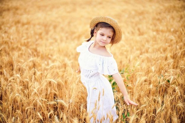 Gelukkig kind op het gebied van de de herfsttarwe. mooi meisje in witte jurk en strooien hoed veel plezier met spelen, oogsten Premium Foto