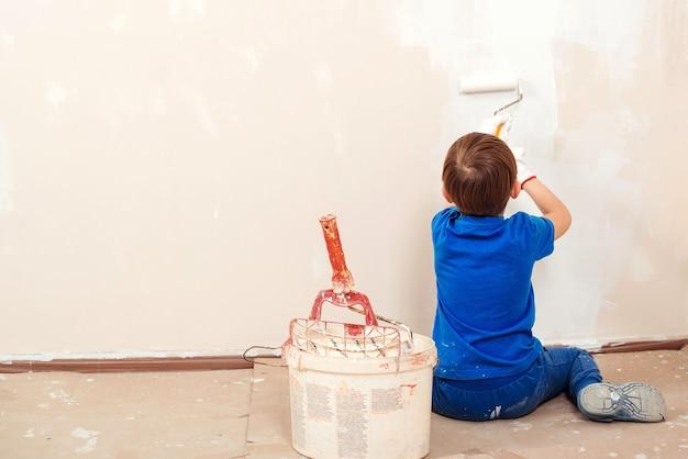 Gelukkig kind schildert de muur. reparatie in het appartement. leuke jongen met een verfroller. nieuw huis voor familie. Premium Foto