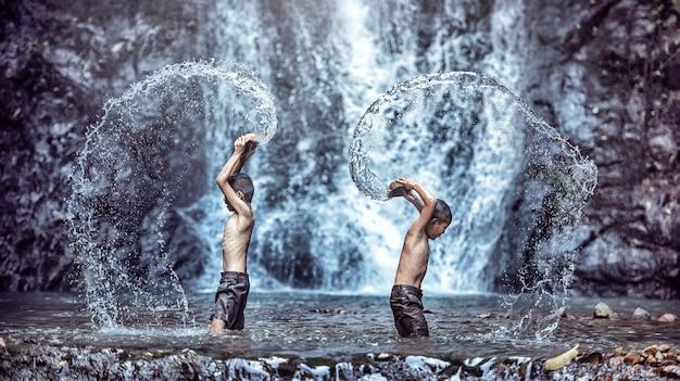 Gelukkig kind spelen bij waterval. kid plezier buitenshuis. Premium Foto