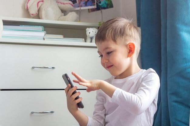 Gelukkig kind videobellen via smartphone naar zijn vader, moeder, opa, oma. blijf thuis, sociale afstand en zelfisolatie tijdens quarantaineconcept. Premium Foto