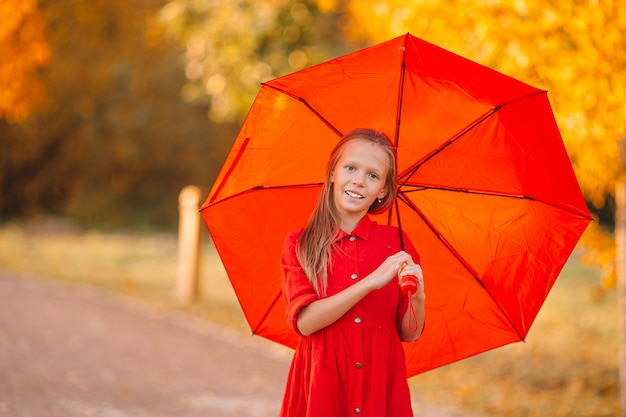 Gelukkig kindmeisje lacht onder rode paraplu Premium Foto