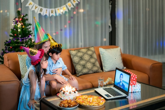 Gelukkig klein meisje en zoon vieren verjaardag met haar moeder thuis met vader op videogesprek Premium Foto