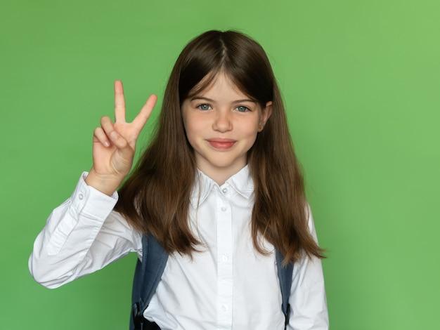 Gelukkig klein schoolmeisje dat teken v, terug naar schoolconcept toont Premium Foto