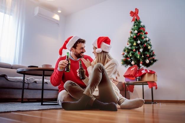 Gelukkig knap kaukasisch paar met santahoeden op hoofden die op de vloer met bierfles zitten in handen en geknuffel. op de achtergrond is de kerstboom met cadeautjes eronder. woonkamer interieur. Premium Foto
