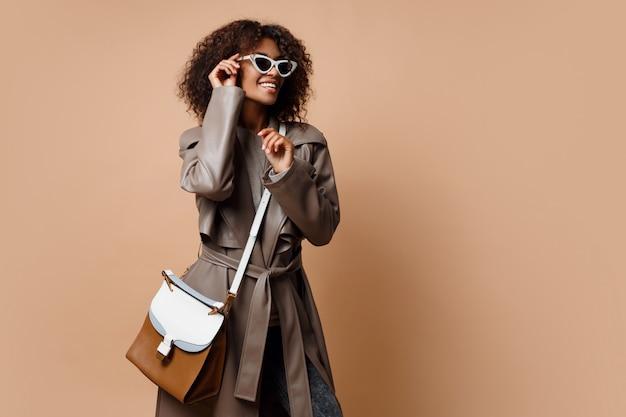 Gelukkig knap zwarte die grijze leerlaag dragen, die op beige achtergrond stellen. herfst of winter mode concept. Gratis Foto