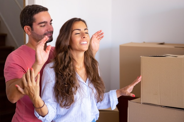Gelukkig knappe man leidt zijn vriendin met gesloten ogen naar hun nieuwe appartement met kartonnen dozen Gratis Foto