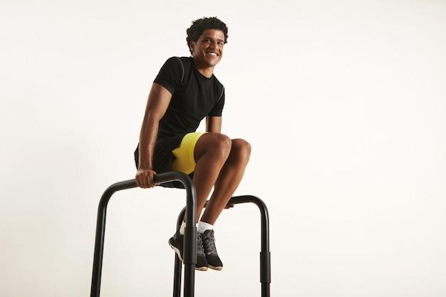 Gelukkig lachend afro-amerikaanse man in zwarte synthetische trainingstoestel thuis oefenen op parallelle staven, geïsoleerd op wit Gratis Foto