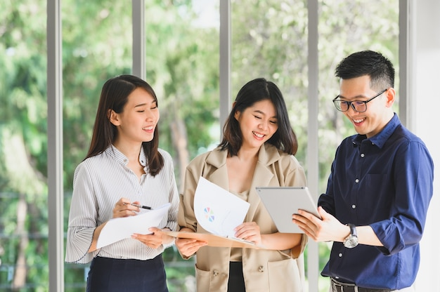 Gelukkig lachend aziatische business team bespreken en brainstormen samen op kantoor Premium Foto
