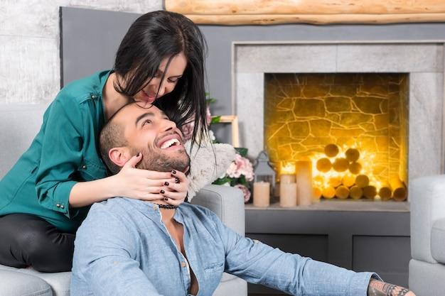 Gelukkig lachend internationale paar man met baard en zijn brunette zwangere vrouw zittend op de bank en hem knuffelen in de woonkamer met een open haard Premium Foto
