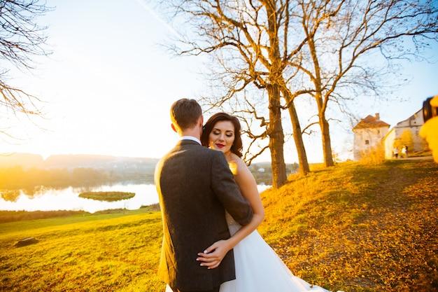 Gelukkig lachend jonggehuwden buiten lopen, zoenen en omhelzen op hun trouwdag Premium Foto